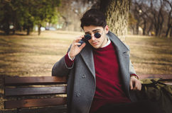 Νέο αρσενικό hipster με τα γυαλιά ηλίου που κάθονται στο πάρκο Στοκ εικόνα με δικαίωμα ελεύθερης χρήσης