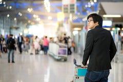 Νέο ασιατικό άτομο με τις αποσκευές στο τερματικό αερολιμένων Στοκ Φωτογραφίες