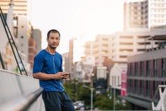 Νέο ασιατικό άτομο που ακούει τη μουσική πριν από ένα τρέξιμο πόλεων Στοκ Φωτογραφίες