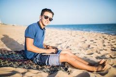 Νέο ασιατικό άτομο που εργάζεται με το φορητό προσωπικό υπολογιστή στην τροπική παραλία Τουρίστας Στοκ φωτογραφίες με δικαίωμα ελεύθερης χρήσης