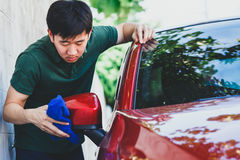 Νέο ασιατικό άτομο που καθαρίζει και που πλένει ένα αυτοκίνητο σε υπαίθριο Στοκ εικόνα με δικαίωμα ελεύθερης χρήσης