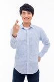 Νέο ασιατικό άτομο που παρουσιάζει τυχερό σημάδι. Στοκ Φωτογραφία