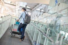 Νέο ασιατικό άτομο που περπατά με το καροτσάκι στο τερματικό αερολιμένων Στοκ Εικόνα