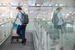 Νέο ασιατικό άτομο που περπατά με το καροτσάκι στο τερματικό αερολιμένων Στοκ φωτογραφίες με δικαίωμα ελεύθερης χρήσης