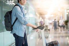 Νέο ασιατικό άτομο που περπατά με το καροτσάκι στο τερματικό αερολιμένων Στοκ φωτογραφία με δικαίωμα ελεύθερης χρήσης