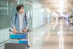 Νέο ασιατικό άτομο που περπατά με το καροτσάκι στο τερματικό αερολιμένων Στοκ Εικόνες