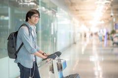 Νέο ασιατικό άτομο που περπατά με το καροτσάκι στο τερματικό αερολιμένων Στοκ εικόνα με δικαίωμα ελεύθερης χρήσης