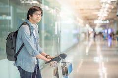 Νέο ασιατικό άτομο που περπατά με το καροτσάκι στο τερματικό αερολιμένων Στοκ Φωτογραφία