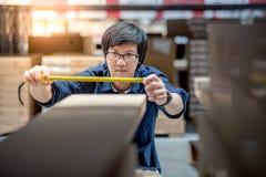 Νέο ασιατικό άτομο που χρησιμοποιεί το μέτρο ταινιών με το κουτί από χαρτόνι Στοκ Εικόνες