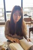 Νέο ασιατικό βιβλίο ανάγνωσης κοριτσιών το πρωί Στοκ φωτογραφίες με δικαίωμα ελεύθερης χρήσης
