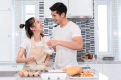 Νέο ασιατικό ζεύγος ανδρών και γυναικών που κατασκευάζει μαζί το κέικ αρτοποιείων στοκ εικόνα