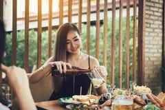 Νέο ασιατικό θηλυκό που έχει τη διασκέδαση στην κατανάλωση με ενθαρρυντικό με την μπύρα στο εστιατόριο στοκ φωτογραφία