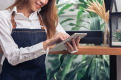 Νέο ασιατικό θηλυκό barista χρησιμοποιώντας την ηλεκτρονική ταμπλέτα στη καφετερία της takeing το σπάσιμο το θερμό απόγευμα Στοκ φωτογραφία με δικαίωμα ελεύθερης χρήσης