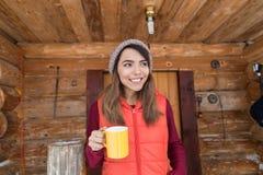 Νέο ασιατικό κορίτσι πεζουλιών εκμετάλλευσης φλυτζανιών στο καυτό καφέ χειμερινό θέρετρο εξοχικών σπιτιών τσαγιού ξύλινο Στοκ Εικόνες