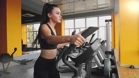 Νέο ασιατικό κορίτσι που κάνει τον αθλητισμό στον ελλειπτικό εκπαιδευτή στη γυμναστική φιλμ μικρού μήκους