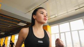 Νέο ασιατικό κορίτσι που κάνει τον αθλητισμό στον ελλειπτικό εκπαιδευτή στη γυμναστική απόθεμα βίντεο