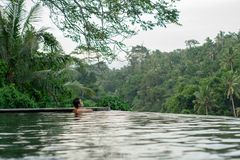 Νέο ασιατικό κορίτσι που κολυμπά στη λίμνη απείρου με την όμορφη άποψη στοκ φωτογραφία με δικαίωμα ελεύθερης χρήσης