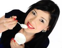 Νέο ασιατικό κορίτσι που τρώει το γιαούρτι Στοκ Φωτογραφία
