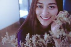 Νέο ασιατικό κορίτσι Smiley που εξετάζει τη κάμερα με τα ξηρά λουλούδια Στοκ φωτογραφία με δικαίωμα ελεύθερης χρήσης