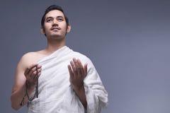 Νέο ασιατικό μουσουλμανικό άτομο που φορά ihram τα ενδύματα με τις χάντρες προσευχής Στοκ Εικόνες