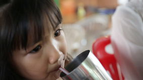 Νέο ασιατικό παιδί που πίνει ένα ποτήρι του νερού απόθεμα βίντεο