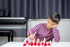 Νέο ασιατικό σκάκι παιχνιδιού αγοριών στο δωμάτιο Στοκ Φωτογραφία