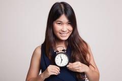 Νέο ασιατικό χαμόγελο γυναικών με ένα ρολόι Στοκ Εικόνα