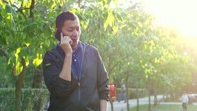 Νέο ασιατικό όμορφο άτομο που μιλά στο τηλέφωνο στο θερινό ηλιόλουστο πάρκο απόθεμα βίντεο