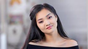 Νέο ασιατικό όμορφο κορίτσι πορτρέτου κινηματογραφήσεων σε πρώτο πλάνο που φορά το φυσικό makeup και το φρέσκο δέρμα που εξετάζου απόθεμα βίντεο