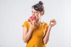Νέο αστείο πρότυπο brunette με τα donuts που θέτουν το στούντιο που πυροβολείται υπόβαθρο, που δεν απομονώνεται στο άσπρο στοκ εικόνες με δικαίωμα ελεύθερης χρήσης