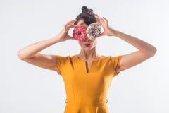 Νέο αστείο πρότυπο brunette με τα donuts που θέτουν το στούντιο που πυροβολείται υπόβαθρο, που δεν απομονώνεται στο άσπρο στοκ φωτογραφία με δικαίωμα ελεύθερης χρήσης