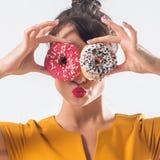 Νέο αστείο πρότυπο brunette με τα donuts που θέτουν το στούντιο που πυροβολείται υπόβαθρο, που δεν απομονώνεται στο άσπρο στοκ εικόνα με δικαίωμα ελεύθερης χρήσης