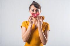 Νέο αστείο πρότυπο brunette με τα donuts που θέτουν το στούντιο που πυροβολείται στο άσπρο υπόβαθρο, όχι στοκ εικόνες