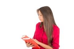Νέο λατινικό κορίτσι που εξετάζει τις καλύψεις βιβλίων Στοκ Εικόνες