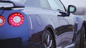 Νέο αυτοκίνητο coupe δεξιά πλευρών σκούρο μπλε στο χώρο στάθμευσης ρόδες πόρτες Παρουσίαση lights red Κρύες σκιές απόθεμα βίντεο
