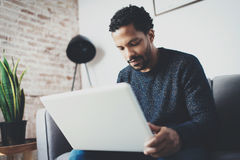 Νέο αφρικανικό άτομο που γράφει το ηλεκτρονικό ταχυδρομείο στο lap-top καθμένος τον καναπέ στο σύγχρονο coworking στούντιό του Έν Στοκ εικόνες με δικαίωμα ελεύθερης χρήσης