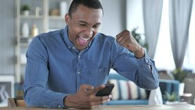 Νέο αφρικανικό άτομο που διεγείρεται για την επιτυχία χρησιμοποιώντας Smartphone στοκ φωτογραφία με δικαίωμα ελεύθερης χρήσης