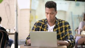 Νέο αφρικανικό άτομο που εργάζεται στο lap-top, υπαίθριος καφές φιλμ μικρού μήκους