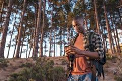 Νέο αφρικανικό άτομο που χρησιμοποιεί το ΠΣΤ πεζοποριες σε ένα δάσος στοκ φωτογραφία με δικαίωμα ελεύθερης χρήσης
