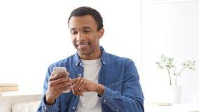 Νέο αφροαμερικανός άτομο που κοιτάζει βιαστικά on-line σε Smartphone Στοκ φωτογραφία με δικαίωμα ελεύθερης χρήσης