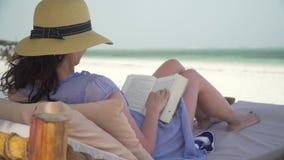 Νέο βιβλίο ανάγνωσης γυναικών στην άσπρη παραλία από τον ωκεανό απόθεμα βίντεο