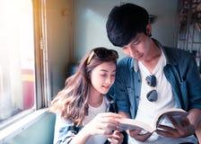 Νέο βιβλίο ανάγνωσης ζευγών και χρησιμοποίηση της ταμπλέτας στοκ εικόνα με δικαίωμα ελεύθερης χρήσης