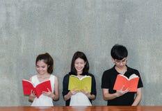 Νέο βιβλίο ανάγνωσης χαμόγελου ομάδας σπουδαστών στοκ φωτογραφίες με δικαίωμα ελεύθερης χρήσης