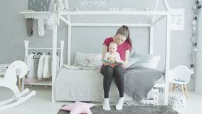 Νέο βιβλίο ανάγνωσης mom στο κορίτσι νηπίων στο βρεφικό σταθμό απόθεμα βίντεο