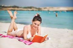 Νέο βιβλίο ανάγνωσης γυναικών στην παραλία θάλασσας στοκ εικόνες με δικαίωμα ελεύθερης χρήσης