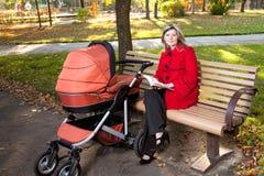 Νέο βιβλίο ανάγνωσης γυναικών στον πάγκο με ένα καροτσάκι Στοκ Φωτογραφίες