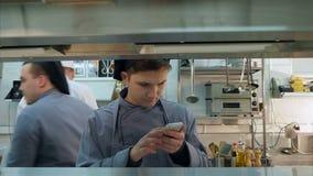 Νέο βοηθητικό κουζινών στο τηλέφωνό του κατά τη διάρκεια της εργασίας απόθεμα βίντεο