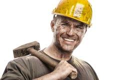 Νέο βρώμικο άτομο εργαζομένων με το σκληρό κράνος καπέλων που κρατά ένα σφυρί Στοκ Φωτογραφία