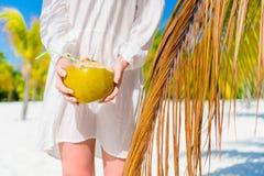 Νέο γάλα καρύδων κατανάλωσης γυναικών την καυτή ημέρα στην παραλία Καρύδα κινηματογραφήσεων σε πρώτο πλάνο στα θηλυκά χέρια κοντά Στοκ Φωτογραφίες