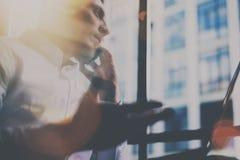 Νέο γενειοφόρο άτομο που κάνει την κινητή κλήση στο σύγχρονο γραφείο Τύπος που φαίνεται έξω το πανοραμικό παράθυρο και που χρησιμ Στοκ φωτογραφίες με δικαίωμα ελεύθερης χρήσης